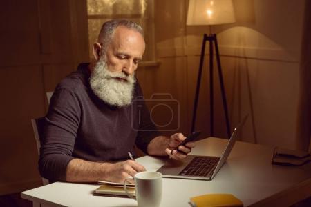 Photo pour Homme aux cheveux gris travaillant à la maison à l'aide d'appareils numériques et ordinateur portable - image libre de droit