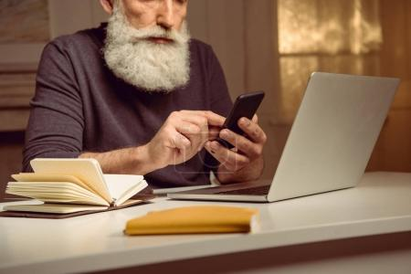 grey haired man using smartphone
