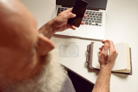 Photo for Overhead view of grey haired man sitting at table and using smartphone - Royalty Free Image