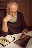 man using smartphone in thoughtful pose