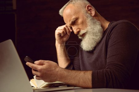 man sitting at table and using smartphone
