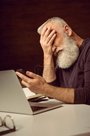man holding smartphone with facepalm