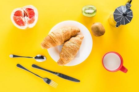 Photo for Top view of fresh croissants on white plate and coffee maker with fruits on yellow - Royalty Free Image
