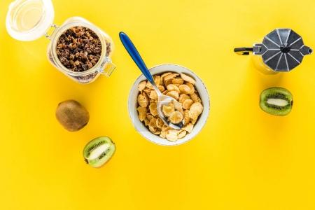 Photo for Top view of cereal flakes in bowl and coffee maker with kiwis and raisins - Royalty Free Image