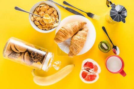 Photo for Top view of tasty healthy breakfast with fruits and croissants on yellow - Royalty Free Image