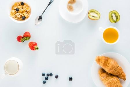 Photo for Top view of tasty breakfast with croissants, coffee and strawberries on tabletop - Royalty Free Image