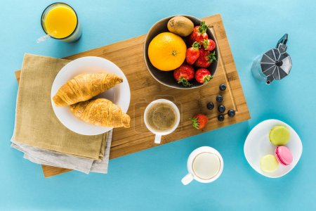 Photo for Top view of croissants with berries on kitchen desk with coffee and orange juice - Royalty Free Image