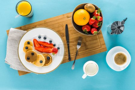 Photo for Top view of pancakes with berries on kitchen desk with coffee and orange juice - Royalty Free Image