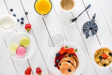 Photo for Top view of pancakes with macarons and coffee with corn flakes on wooden tabletop - Royalty Free Image
