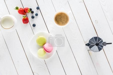 macarons with coffee and strawberries on wooden tabletop