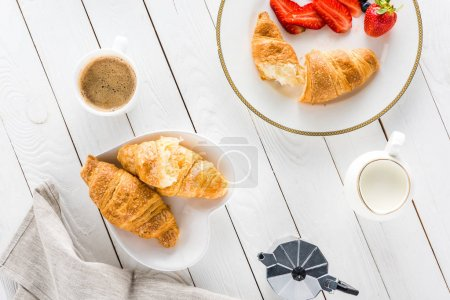 Photo for Top view of croissants with coffee and strawberries on wooden tabletop - Royalty Free Image