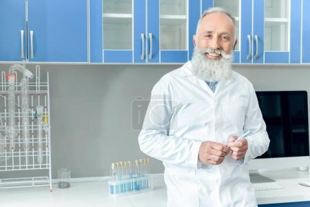 Photo for Happy senior bearded scientist in white coat holding tube with reagent in chemical laboratory - Royalty Free Image