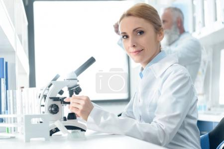 Photo for Caucasian chemist in white coat working with microscope and reagents while looking at camera  in chemical laboratory - Royalty Free Image