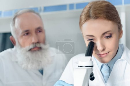 Photo for Concentrated scientists in uniform working together with microscope in chemical lab - Royalty Free Image