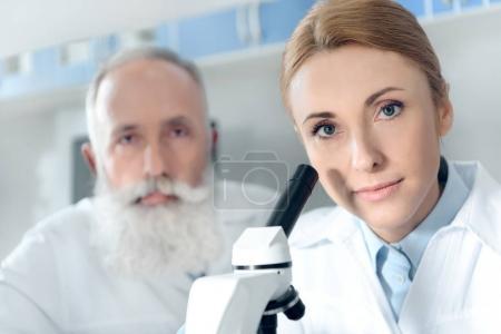 Foto de Dos químicos en batas blancas de trabajo con microscopio y mirando a cámara en laboratorio químico - Imagen libre de derechos
