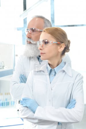 Photo for Two scientists in white coats and goggles looking away and posing in chemical laboratory - Royalty Free Image