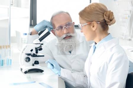 Foto de Equipo de científicos maduros trabajando juntos en el laboratorio y mirando el uno al otro - Imagen libre de derechos