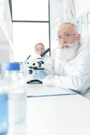 Photo pour Chimistes professionnels en blouse blanche de travail avec des microscopes en laboratoire et en regardant la caméra - image libre de droit