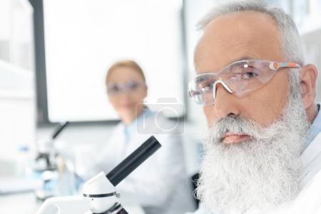Photo pour Gros plan portrait de barbus chercheur travaillant au microscope et en regardant la caméra - image libre de droit