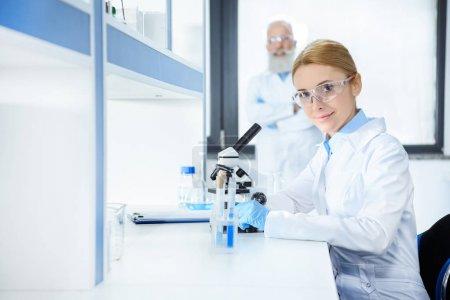 Photo pour Âgés de sourire milieu scientifique en travaillant avec le microscope et collègue debout derrière des lunettes de protection - image libre de droit