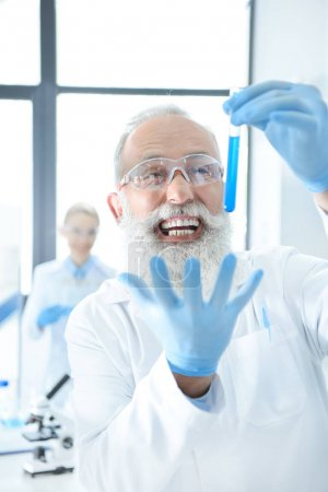 Photo for Excited bearded chemist holding test tube with reagent and gesturing - Royalty Free Image