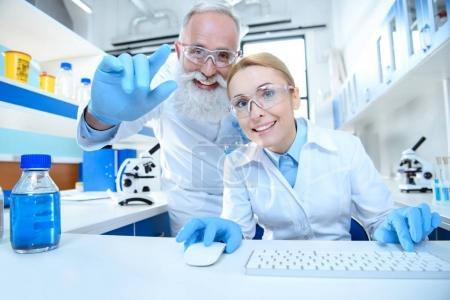 Photo pour Sourire matures scientifiques travaillant de concert avec la souris et le clavier en laboratoire - image libre de droit