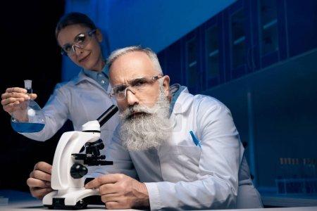 Photo pour Scientifique utilisant un microscope alors que son collègue tient un réactif dans un tube en laboratoire - image libre de droit