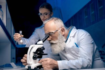 Photo for Scientist using microscope while colleague holding reagent in tube in lab - Royalty Free Image