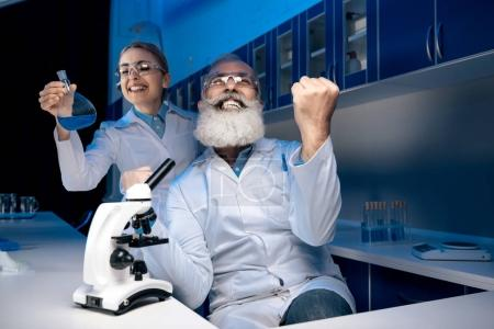 Photo for Scientist using microscope while colleague holding reagent in tube in lab. scientists working together in laboratory - Royalty Free Image