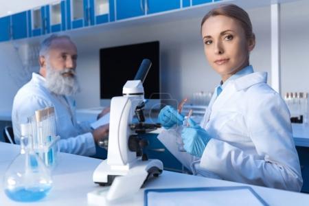 Photo pour Chercheur en blouse blanche et gants de protection regardant la caméra avec collègue près de - image libre de droit
