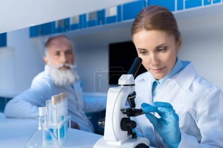 Photo for Focused scientist using microscope while working in lab with colleague behind in lab - Royalty Free Image