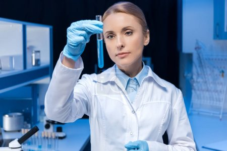 Photo for Pensive laboratory technician looking at tube with reagent at laboratory - Royalty Free Image