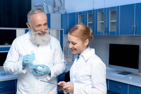 Photo for Smiling chemists in lab coats holding flask and digital tablet at laboratory - Royalty Free Image