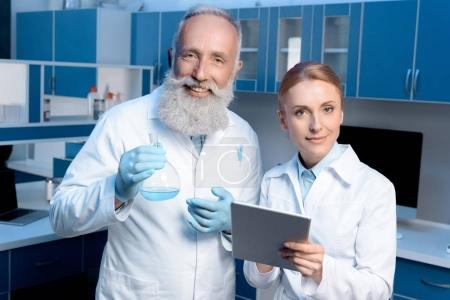 Photo for Smiling chemists in lab coats looking at camera and holding flask and digital tablet - Royalty Free Image