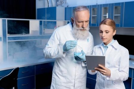 Photo for Thoughtful scientists in lab coats looking at digital tablet in laboratory - Royalty Free Image