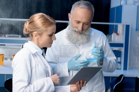 Photo for Pensive scientists in lab coats looking at digital tablet in laboratory - Royalty Free Image