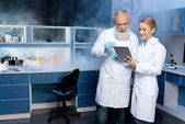 laboratory technicians looking at digital tablet