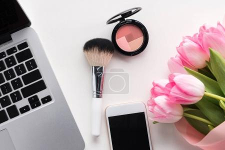 Photo for Flat lay of open laptop, smartphone with blank screen, flowers and makeup brush isolated on white - Royalty Free Image