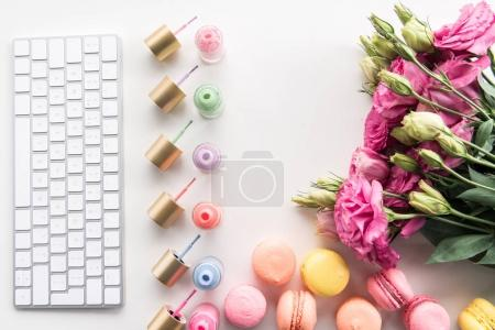 Photo for Flat lay with keyboard, colorful nail polishes, macarons and flowers isolated on white - Royalty Free Image