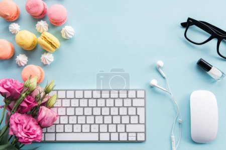 keyboard, macarons and flowers on tabletop