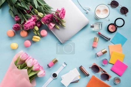 Foto de Vista superior de Ramos de flores con el portátil y las gafas de sol con maqueta de cosméticos - Imagen libre de derechos