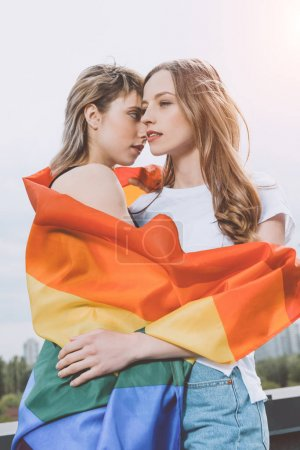 Photo for Sensual young lesbian couple posing with lgbt flag outdoors - Royalty Free Image