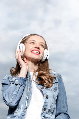 Foto de Retrato de sonriente escuchar música chica en auriculares bajo el cielo - Imagen libre de derechos