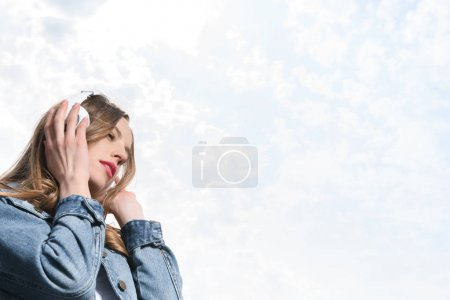Photo pour Belle fille coûteuse écouter de la musique dans les écouteurs sous le ciel - image libre de droit