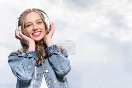 Photo pour Portrait de jeune femme souriante écoutant de la musique dans des écouteurs sous le ciel - image libre de droit