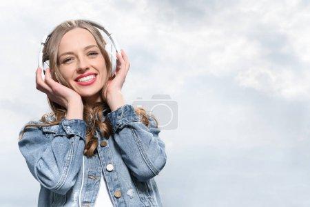 Smiling woman listening music in headphones