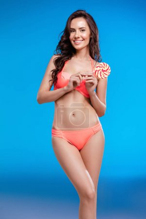 Girl in swimsuit holding lollipop