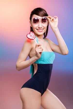 Girl in swimsuit eating candy
