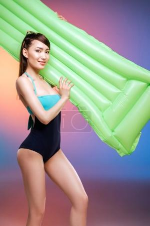 Girl in swimsuit with swimming mattress
