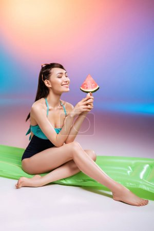 Girl in swimsuit eating watermelon